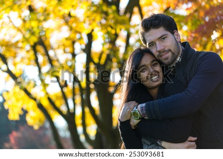 Couple of lovers hugging in front of autumn tree - stock photo