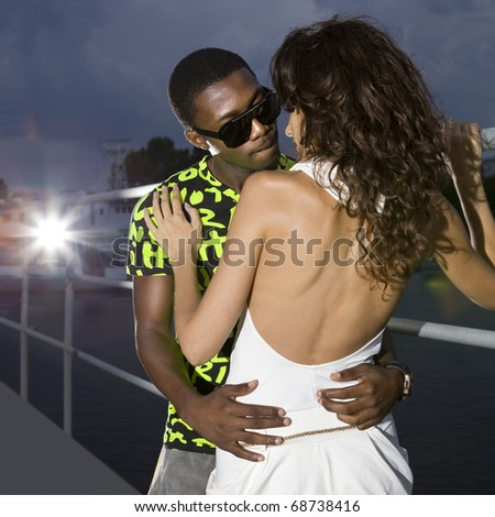 couple of lovers in harbour at night, afro-american man embraces caucasian woman - stock photo