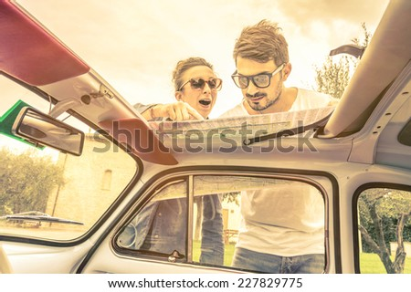 Couple of lovers looking at a map during honeymoon trip vacation - Vintage lifestyle traveling around the world with old retro classic car - Young people enjoying together happy moments of life - stock photo