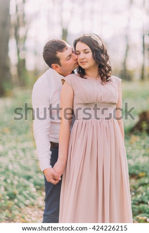Couple of lovers on date in park, young man tenderly hugging from behind his happy smiling girlfriend, kissing her cheek with closed eyes - stock photo