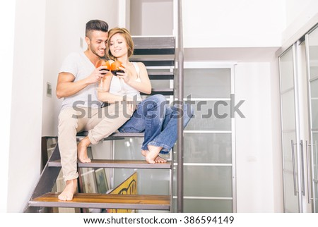 Couple of lovers sitting on a staircase and toasting wine glasses to celebrate - Domestic life, partners relaxing at home - stock photo