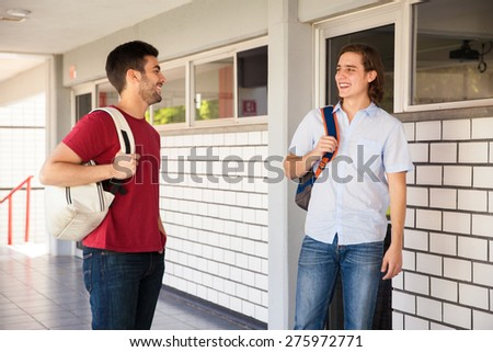 Couple of male friends carrying school bags talking and hanging out in a school hallway - stock photo