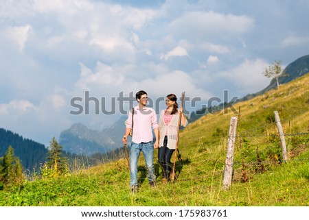 couple of man and woman hiking on mountain summit or alpine grassland in the Bavarian Alps, enjoys the panorama in the leisure time or in vacation - stock photo