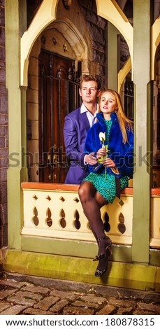 Couple of Man and Woman Looking Forward. Holding a white rose, a attractive young couple is passionately relying on each other outside in winter, looking forward. Instagram Hefe effect. - stock photo