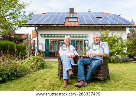 Couple of man and woman sitting in front of their home or house in wicker chairs - stock photo
