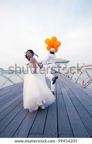couple of man and women in wedding suit glad emotion on wood bridge - stock photo