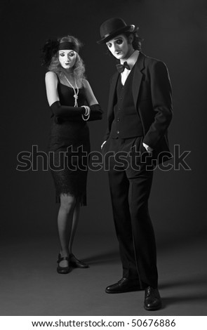 couple of mimes posing against dark background. retro style - stock photo
