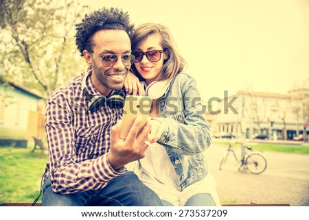 Couple of multiracial lovers looking at smartphone and urban background - Stylish afroamerican guy and beautiful woman watching something funny on phone screen - stock photo