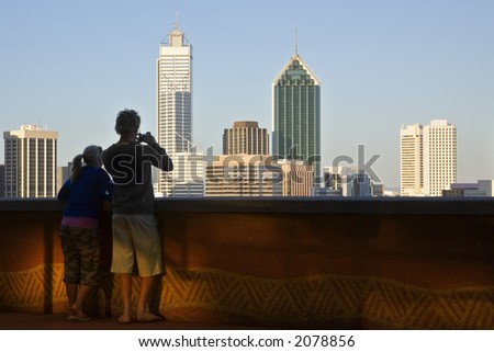 Couple of normal youngsters, not models, with digital camera, photographing Perth skyline at sunset. - stock photo