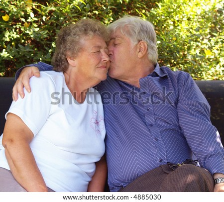 Couple of old swingers having a cuddle - stock photo