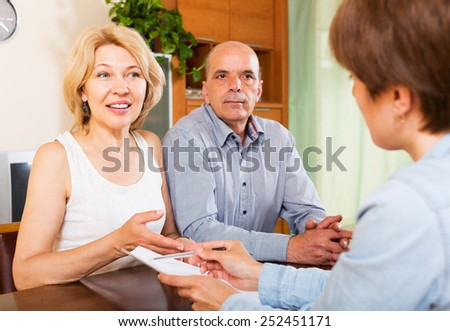 Couple of pensioners talking with manager at home or office