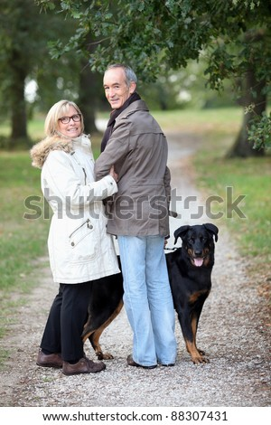 couple of pensioners walking their dog - stock photo