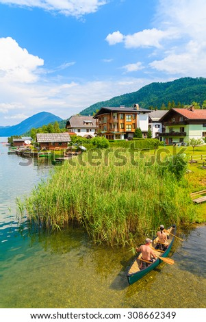 Couple of people in kayak on shore of beautiful Weissensee lake in Alps Mountains, Austria - stock photo
