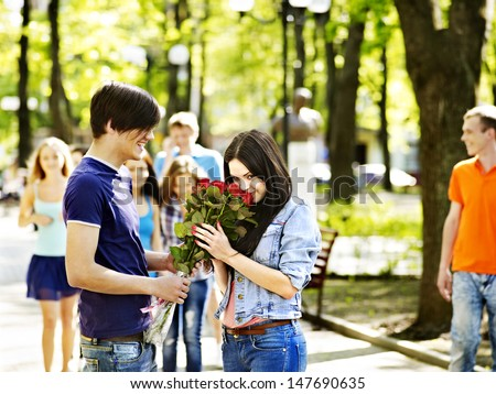 Couple of people on date outdoor. Group of people in background. - stock photo