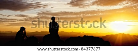 Couple of people viewing the sunset over the desert and mountains in Saguearo National Park - stock photo