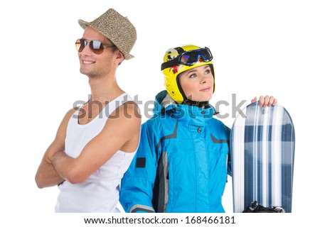 Couple of people with opposite interests. Attractive woman in winter sport costume with snowboard and man in straw hat in white T-shirt