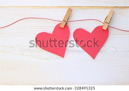 Couple of pink paper hearts pinned on twine, white wooden wall background. Romantic DIY ideas and home decor. - stock photo