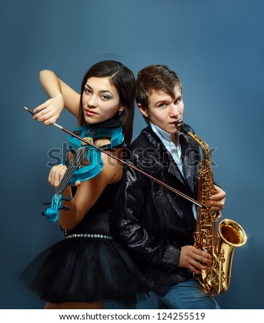 Couple of professional musicians in modern style posing in costumes at studio - stock photo