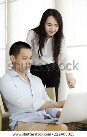 Couple of professionals debating in front of a laptop display - stock photo