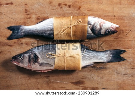 Couple of raw bass fish on the wooden background - stock photo