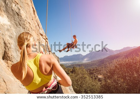 Couple of rock climbers - woman holding man with belay rope against the blue sky and mountains. Stock photo. - stock photo