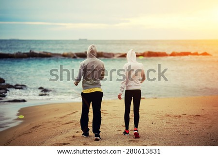Couple of runners walking on the beach resting after intense morning training together, young sporty man and woman talking each to other while taking break after run al the seashore at early morning - stock photo