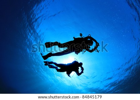 Couple of Scuba Divers silhouetted against sun - stock photo
