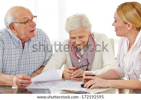 Couple of senior citizens talking to financial consultant about their pension - stock photo
