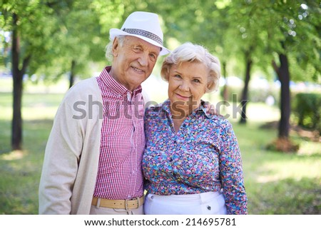 Couple of senior man and woman looking at camera in the park at summer - stock photo