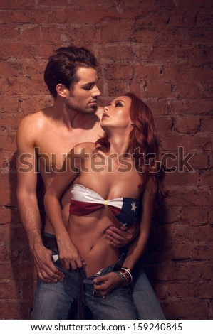 Couple of sexy models posing in fashion shoot. Looking into each other eyes with passion  - stock photo