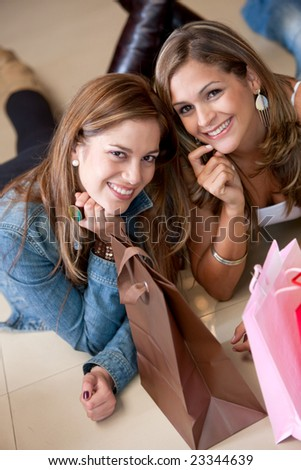 Couple of shopping women lying on the floor smiling with bags - stock photo