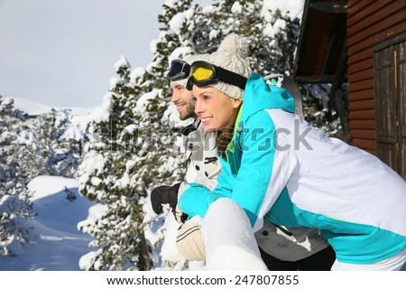 Couple of skiers admiring panorama from log cabin - stock photo