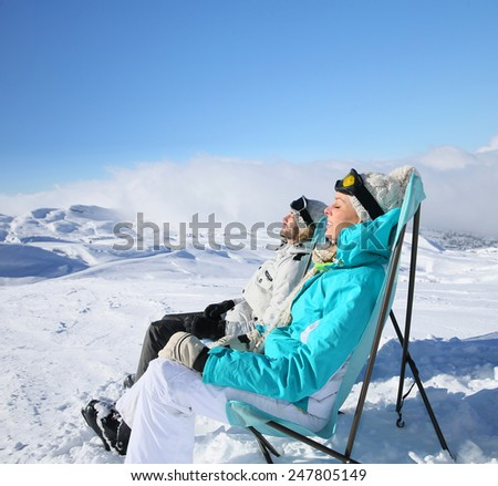 Couple of skiers sunbathing at top of ski slope - stock photo