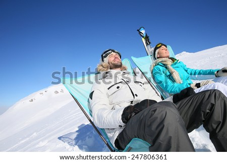 Couple of skiers sunbathing at top of ski slope - stock photo