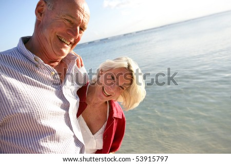 Couple of smiling seniors having a walk by the edge of the sea - stock photo