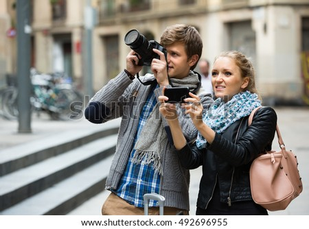 Couple of smiling young tourists making photo with digital camera and mobile phone