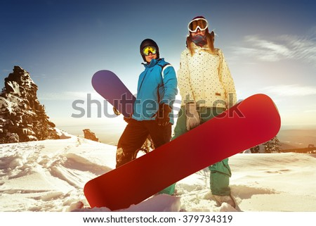 Couple of snowboarders stands in sunset light on mountains top backdrop. Sheregesh resort, Siberia, Russia  - stock photo