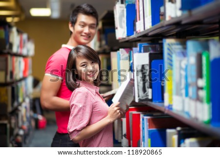 Couple of student spending time in library together - stock photo