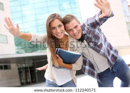 Couple of students having fun in front of university building - stock photo