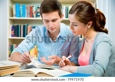couple of students in a library - stock photo