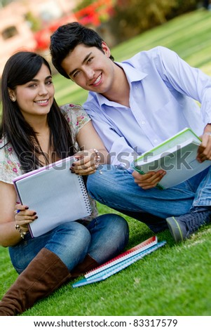 Couple of students sitting outdoors and talking - stock photo