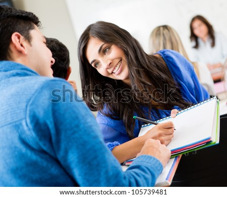 Couple of students talking in class and smiling - stock photo