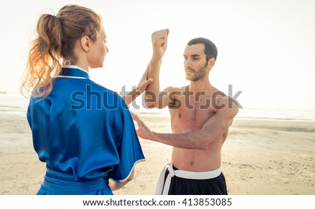 Couple of students training martial arts on the beach. parry and hit in kung fu style - stock photo