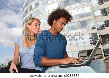 Couple of students working on laptop computer - stock photo