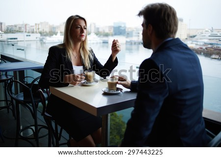 Couple of successful influential leaders having meeting discussion while they drinking cafe, business people talking to each other during coffee break in modern luxury place with sea marina port view - stock photo