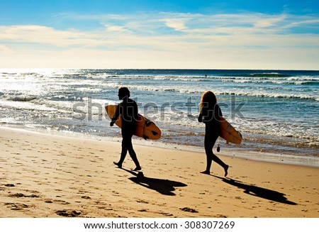 Couple of surfers walking on the ocean beach.  Sagres, Algarve, Portrugal - stock photo
