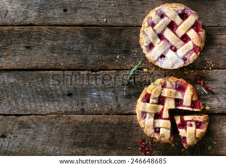 Couple of tart cakes stuffed with pomegranate jam in tray from above on wooden background  - stock photo