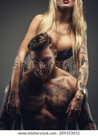 Couple of tattooed male and female. Isolated on grey background.
