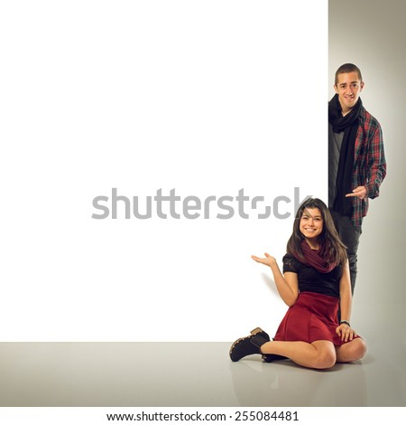 Couple of teenage friends pointing at a blank notice board - stock photo