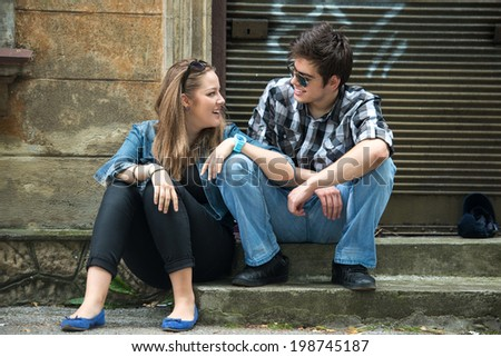Couple of teenagers flirting sitting on the street